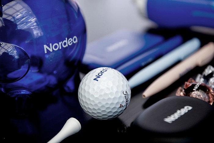 Spargris, golfboll och pennor med Nordeas logo