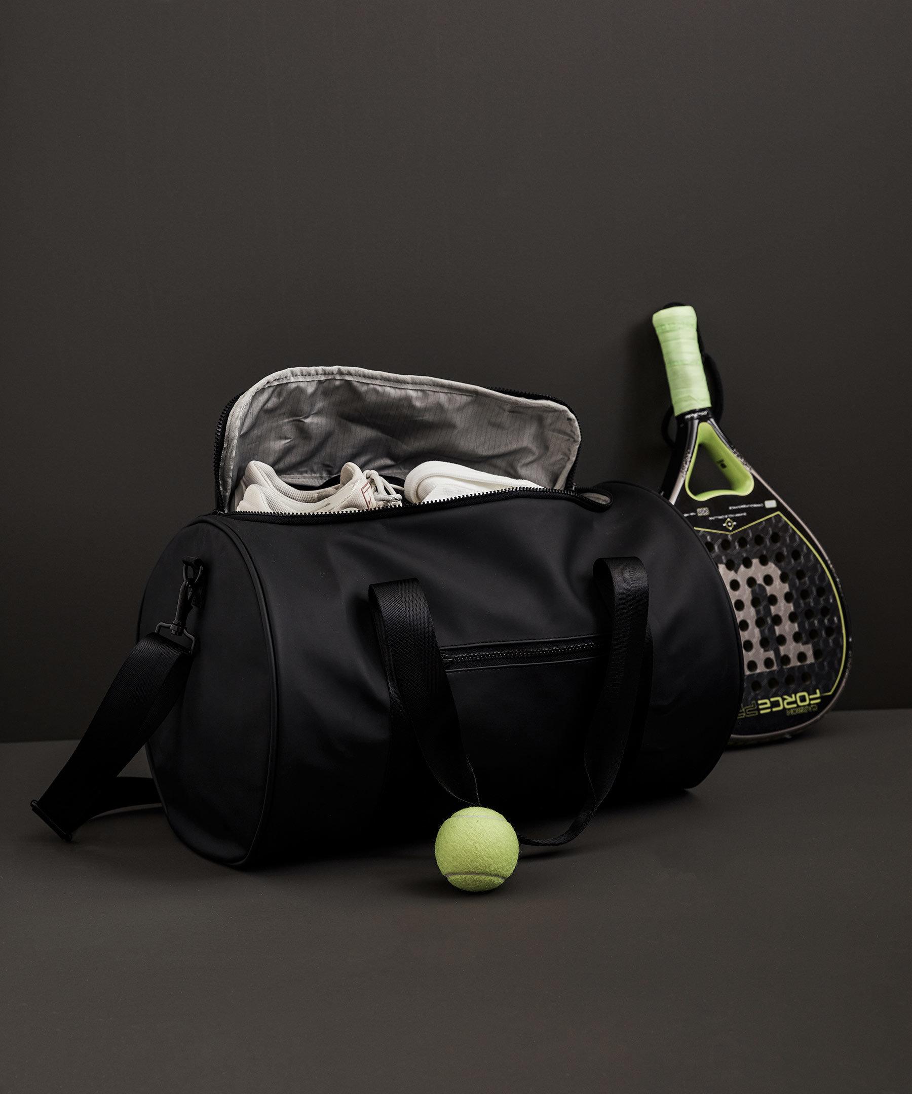 Svart väska, padelrack och padelboll
