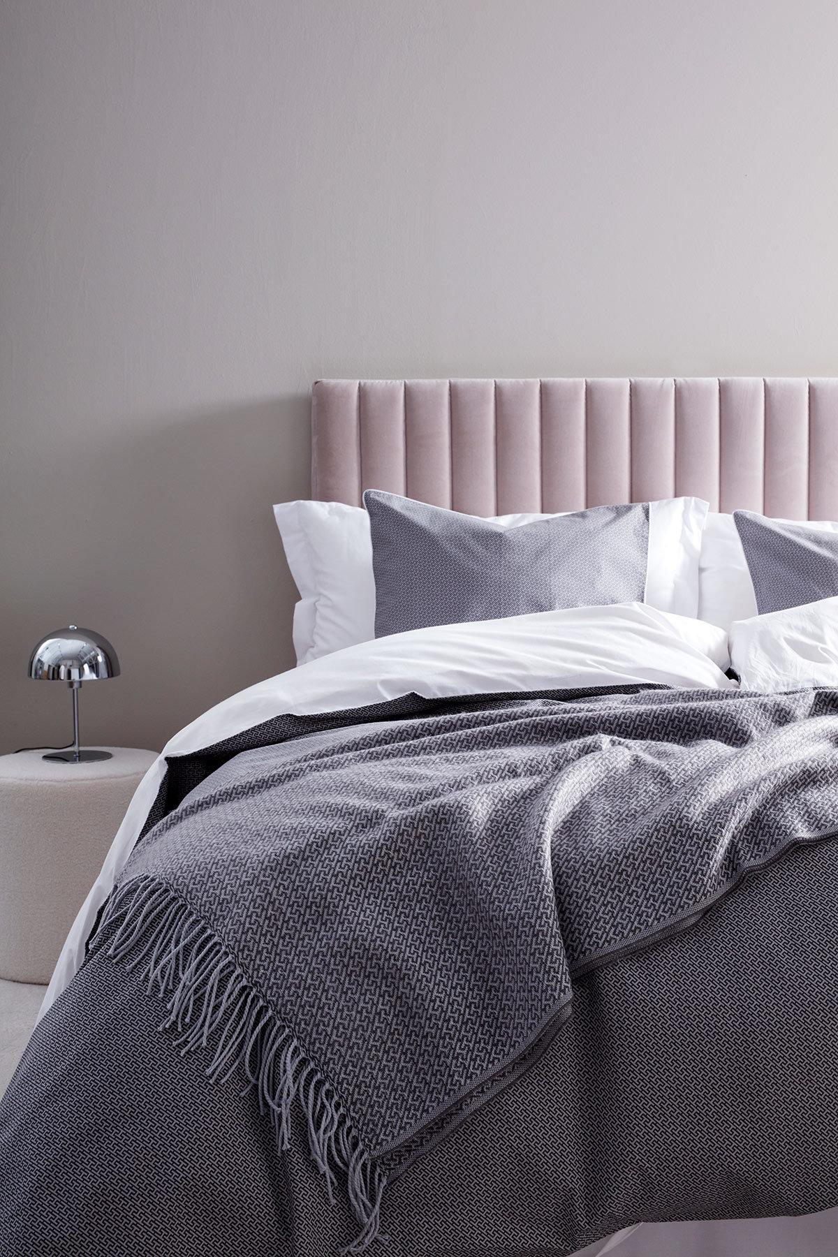 Grått bäddset och pläd, samt rosa sänggavel