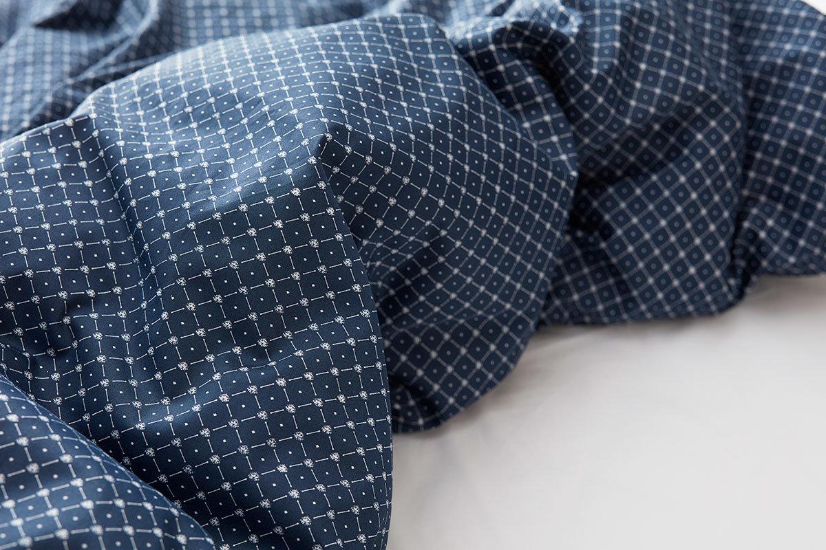 Mörkblå sängkläder i säng