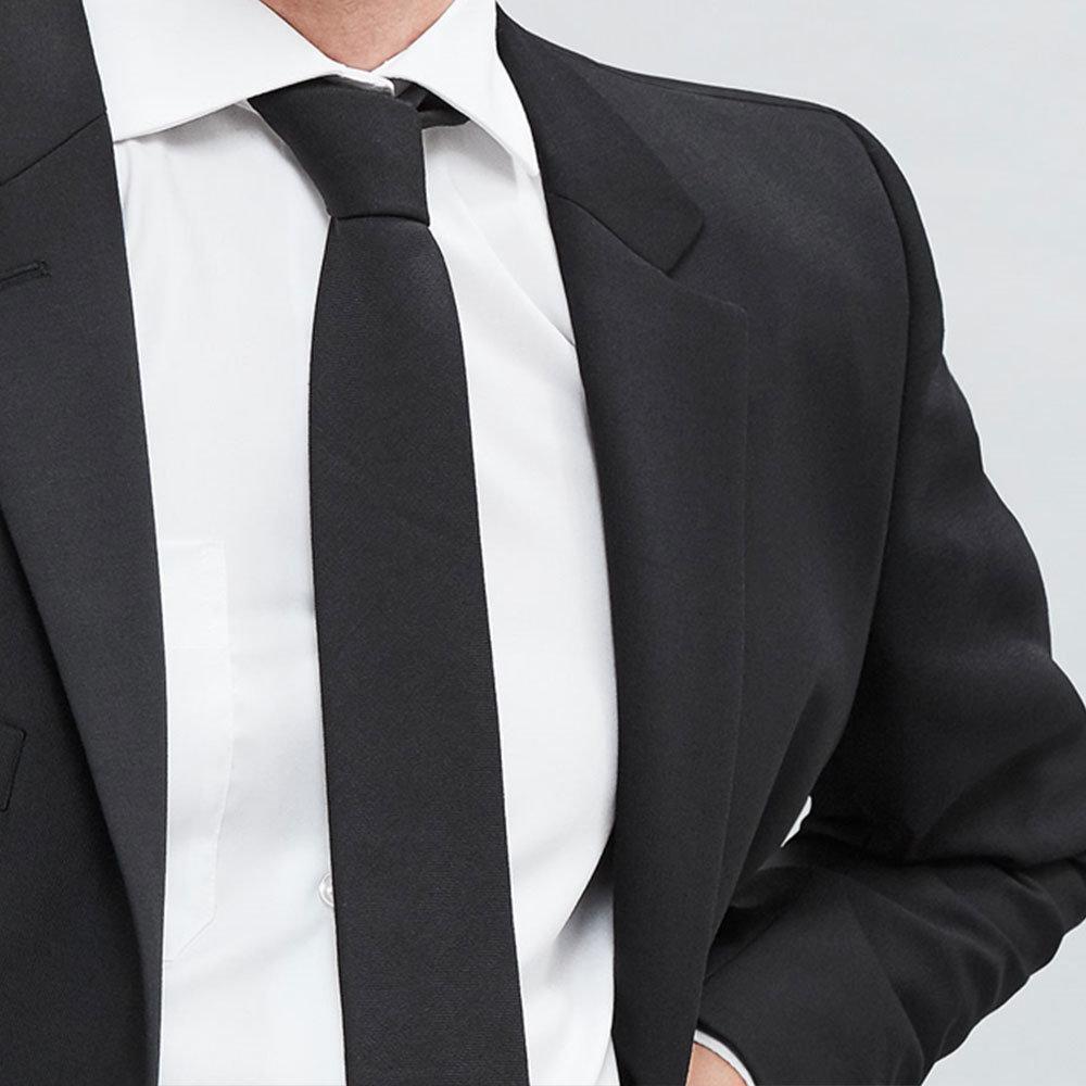 närbild på person i vit skjorta, svart kavaj och svart slips