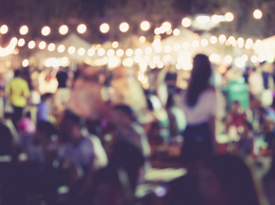 Suddig bild på samling människor i festlig utomhusmiljö