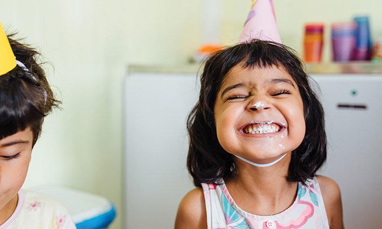 Jente som smiler med bursdagshatt og kake rundt munnen
